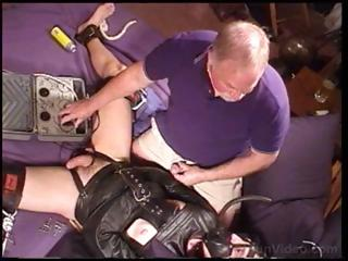 Dude in a leather straitjacket is fondled and teased by old guy