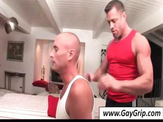 Buff masseur sets up his table with an increment of helps his bald gay consumer strip